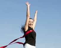 Woman crossing finishing line. Successful beautiful young woman crossing finishing line Stock Image