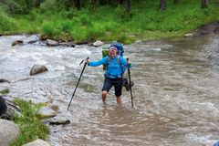 Woman is crossing mountain reiver on foot without shoes Stock Images