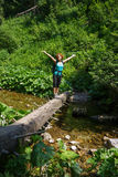 Woman crossing a mountain river Stock Photo