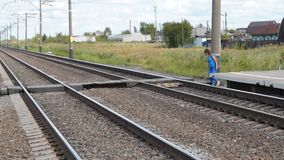 Woman crossing rail tracks after arrival to the station. Woman leaving platform and crossing rail tracks looking around for safe crosswalk stock footage