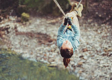Woman crossing a river with tyrolean traverse Stock Photo