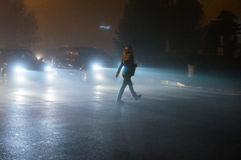 Woman crossing road in fog Stock Image