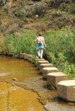 Woman crossing a stream on concrete piles, hiking in the Sierra Norte de Sevilla Natural Park, Spain Stock Photos