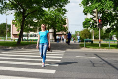 Woman crossing street is dangerous at red light Royalty Free Stock Image