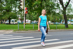 Woman crossing street is dangerous at red light. Woman crossing the street is dangerous at a red light Stock Photography