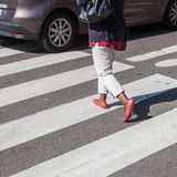 Woman crossing a street Stock Photography