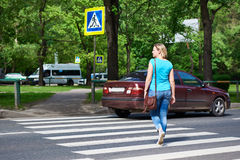 Woman crossing street at pedestrian crossing Royalty Free Stock Image