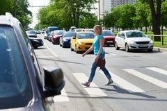 Woman crossing street at pedestrian crossing. Woman crossing the street at a pedestrian crossing Royalty Free Stock Photos