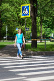 Woman crossing street at pedestrian crossing. Woman crossing the street at a pedestrian crossing Stock Images