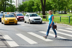 Woman crossing street at pedestrian crossing. Woman crossing the street at a pedestrian crossing Stock Photo