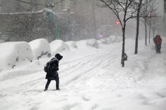 Woman crossing street during snow blizzard Jonas in the Bronx stock photo
