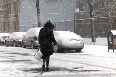 Woman crossing street during snow storm Stock Images
