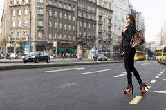 Woman crossing the street. Young woman crossing the street in the city Stock Photo