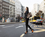 Woman crossing the street. Young woman crossing the street in the city Stock Image