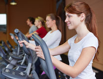 Woman on crosstrainer in fitness. Young women exercising on a crosstrainer in fitness center Royalty Free Stock Images