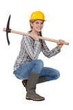 Woman crouching with axe. Woman crouching with a pick-ax Stock Images