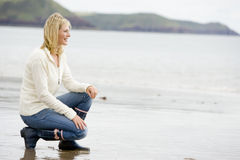 Woman crouching on beach Royalty Free Stock Photos