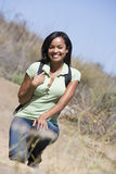Woman crouching on beach path smiling stock images