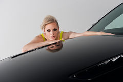 Woman crouching behind a black car Royalty Free Stock Photo