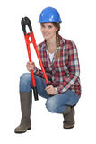 Woman crouching with bolt cutters. Female manual worker crouching with bolt cutters Stock Photography