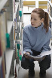 Woman Crouching By Bookshelf In Library Royalty Free Stock Image
