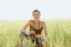Woman Crouching In Field Of Grass Royalty Free Stock Photography