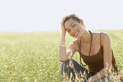 Woman Crouching In Field Of Grass. Portrait of young woman crouching in field of grass Stock Photography