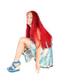 Woman crouching on floor. A woman in a dress and heels with long red hair crouching on the floor Stock Photography