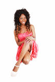 Woman crouching on floor. A lovely young Jamaican woman in a pink dress and long curly hair Royalty Free Stock Photography