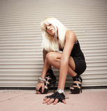 Woman crouching on the ground. Attractive young woman in a crouching position Stock Image