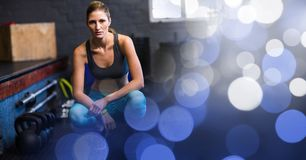 Woman crouching in gym and blue bokeh transition Royalty Free Stock Image