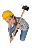 Woman crouching with hammer. Woman crouching whilst holding a sledge hammer Royalty Free Stock Image