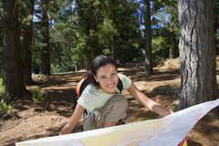 Woman crouching on lakeside woodland trail, looking at map, smiling, front view, portrait Royalty Free Stock Photography