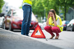 Woman Crouching Near Triangular Warning Sign Stock Images