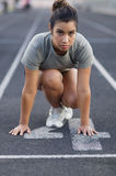 Woman in crouching position at start of race. Attractive woman preparing to run in race as she crouches down on the starter line Royalty Free Stock Photo