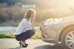 Woman crouching on the road next to a car. Sad person. Damaged car. Natural background. Car accident. Stock Images