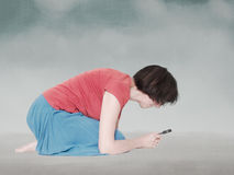 Woman crouching to study something under the magnifying glass. Royalty Free Stock Image
