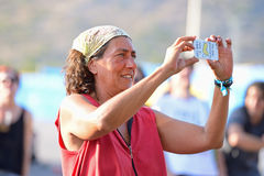 A woman from the crowd takes a picture with her smartphone camera at FIB Festival Royalty Free Stock Photo