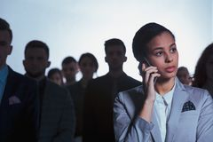Woman in a crowd. Young serious businesswoman talking on a phone in crowd of blurry people Royalty Free Stock Image