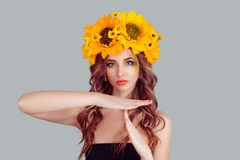 Woman in crown from sunflowers making a timeout gesture stock photography