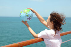 Woman on cruise liner deck holding globe Royalty Free Stock Images
