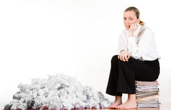 Woman with crumpled papers. Businesswoman with pile of crumpled papers sitting on a stack of paperwork royalty free stock images