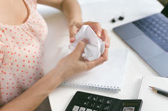Woman crumpling paper in the workplace in front of a laptop royalty free stock photo