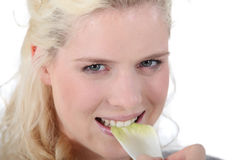 Woman crunching a leaf of endive Stock Image