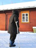 Woman with crutch. Overweight woman with crutch in fornt of a red house on a winter day Stock Photo