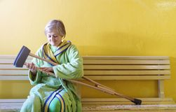 Woman with crutches. Senior woman injured sitting in the hallway of hospital holding crutches Stock Photography