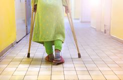 Woman with crutches. Senior woman injured sitting in the hallway of hospital holding crutches Stock Image