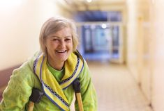 Woman with crutches. Senior woman injured sitting in the hallway of hospital holding crutches Royalty Free Stock Photo