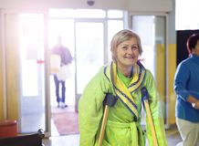 Woman with crutches. Senior woman injured walking through hospital corridor with crutches Stock Images