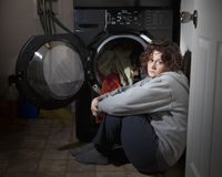 Woman Crying. In the laundry room after being abused Royalty Free Stock Photo